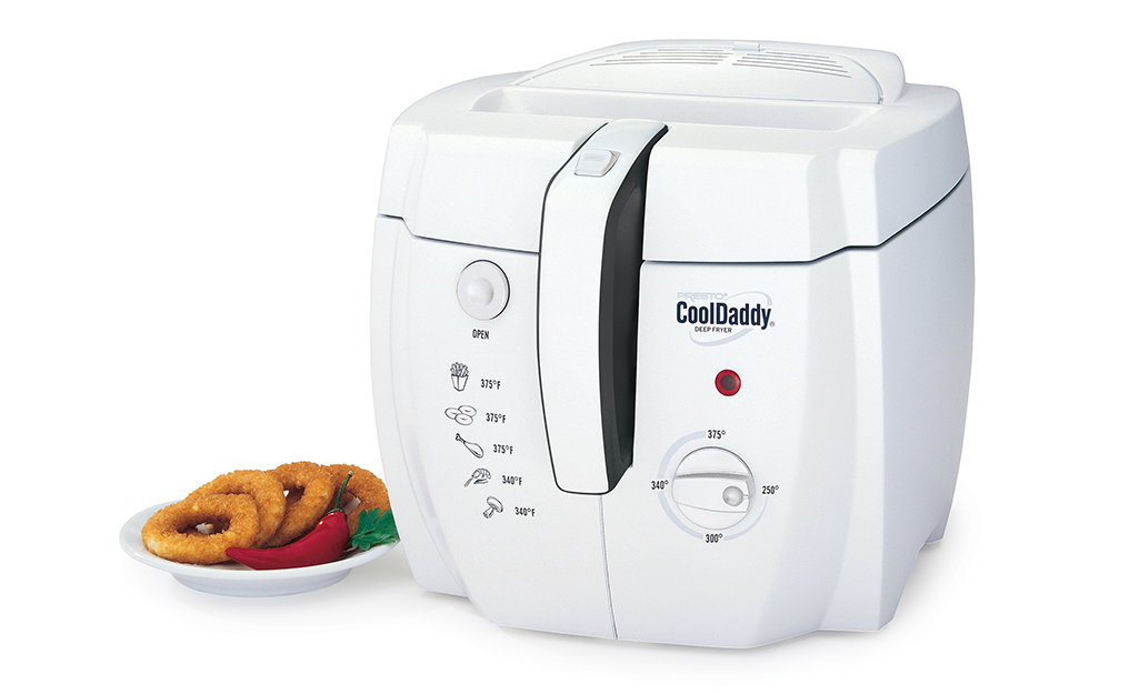 A small, white, cool-touch deep fryers beside a plate of fried onion rings.