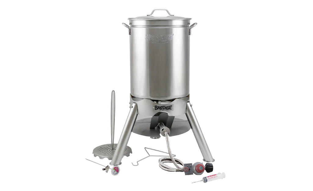 An outdoor deep fryers with a turkey baster, lifting hook and other accessories.