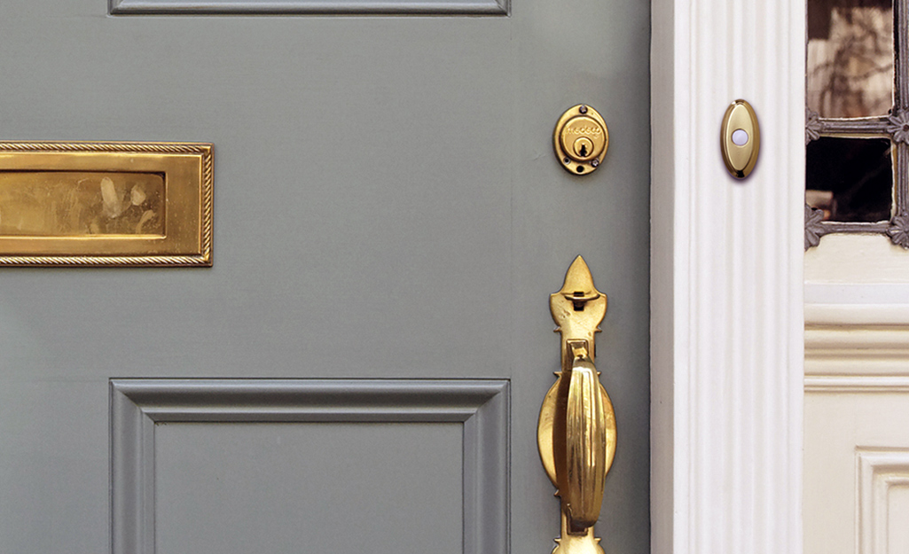A brass wireless doorbell installed next to a front door with brass hardware.