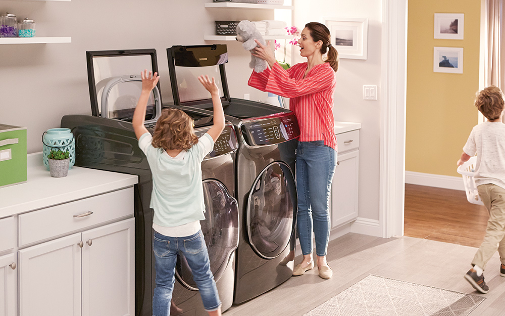 Child helping mom with laundry in the kitchen.