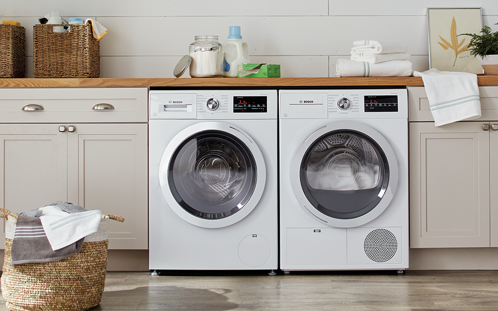 Electric washer and dryer sit next to each other in a laundry room.