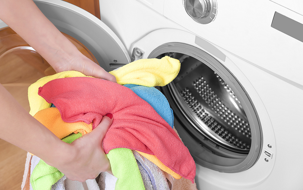 A person grabs a handful of colorful laundry from a dryer.
