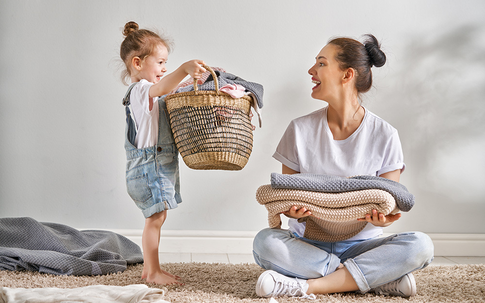 Little girl and her mom folding clothes.