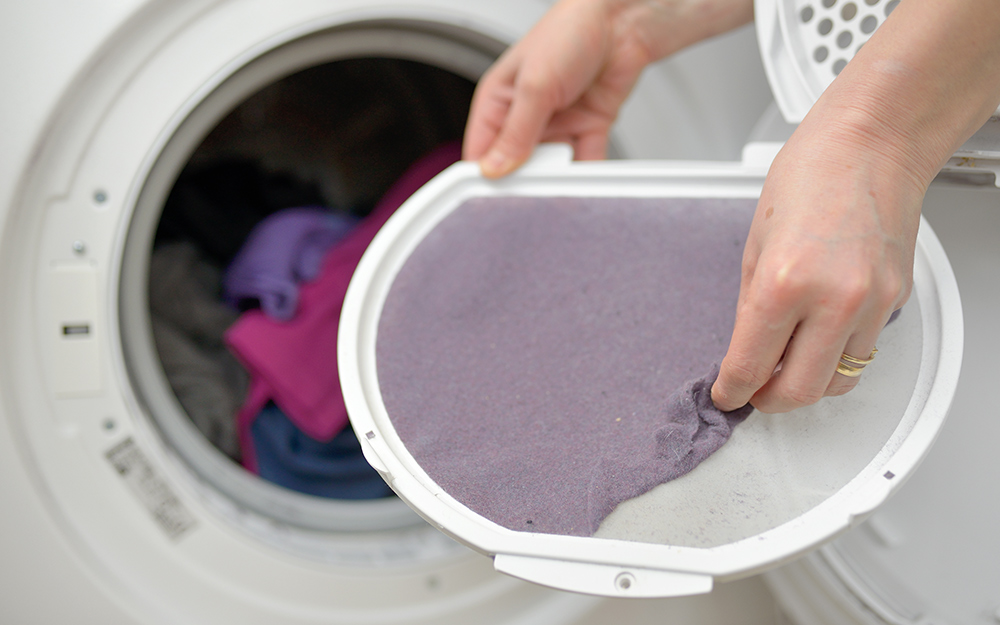 Hand removing and cleaning the dryer lint filter.