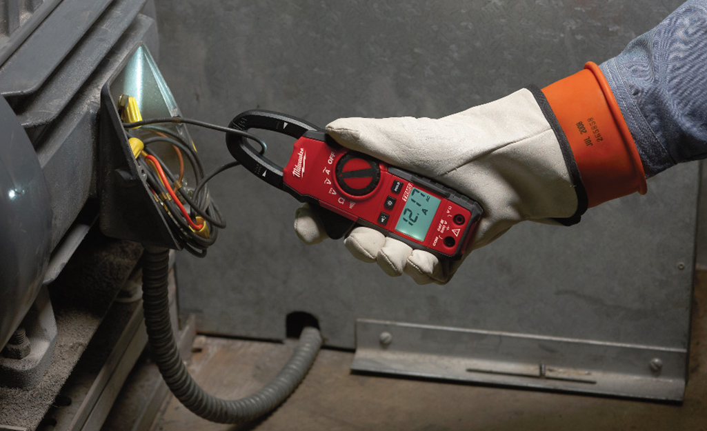 Someone using a clamp meter on a wire.