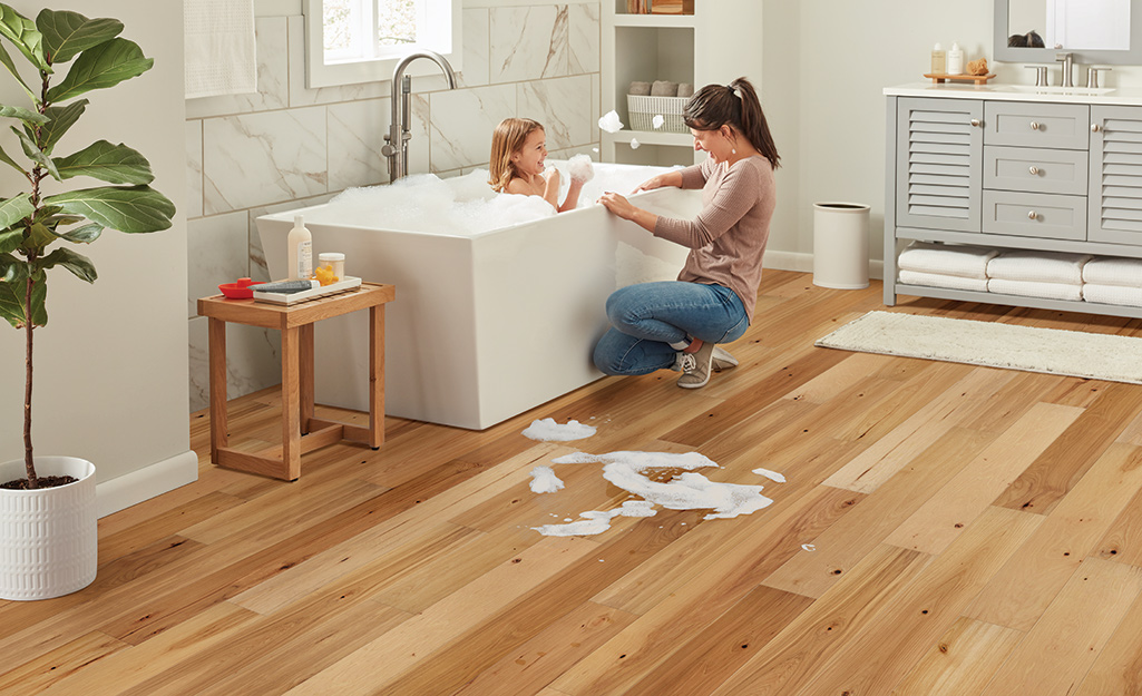 A mother bathing a child in a bathroom with engineered wood floors.