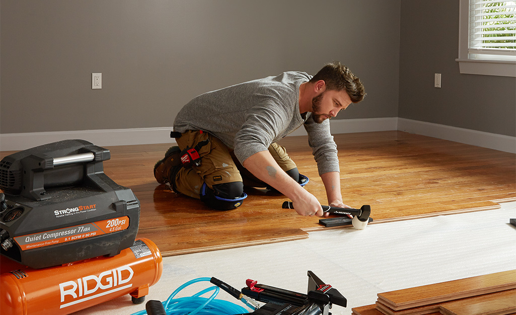 A person installing nail down engineered hardwood floors.
