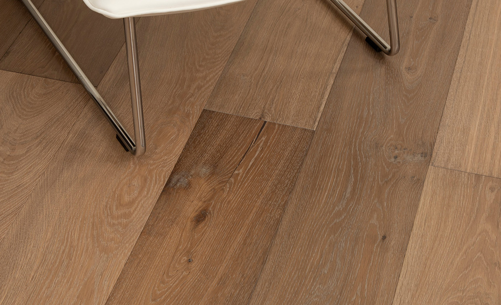 A close up of engineered wood floors with a wire brushed texture.