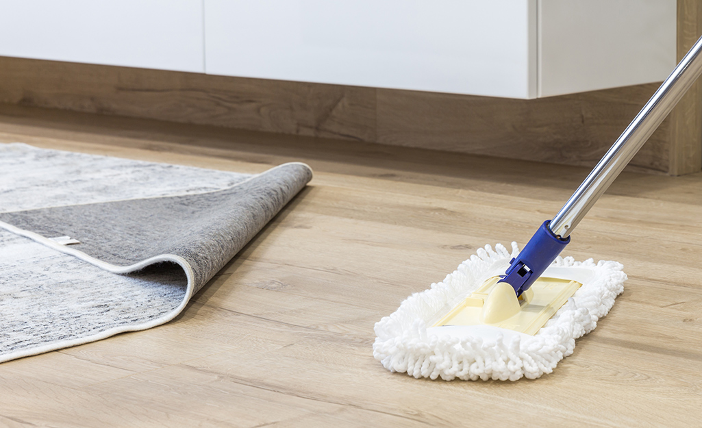 A soft dust mop cleaning an engineered wood floor.