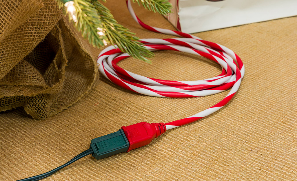 A holiday-themed extension cord powering a Christmas tree.