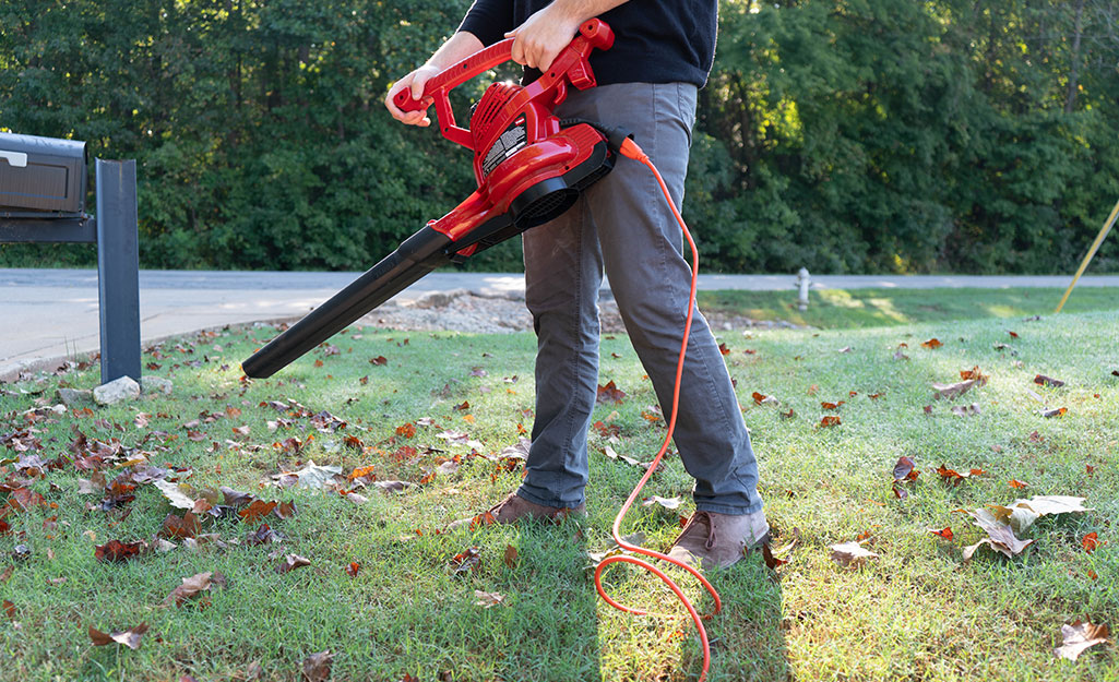 Someone using a leaf blower attached to an outdoor extension cord.