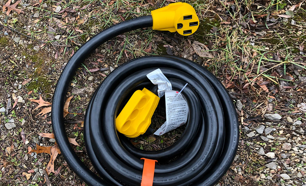 An outdoor extension cord coiled on the ground.