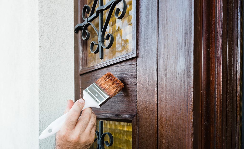 A person applying stain to a wood exterior door.