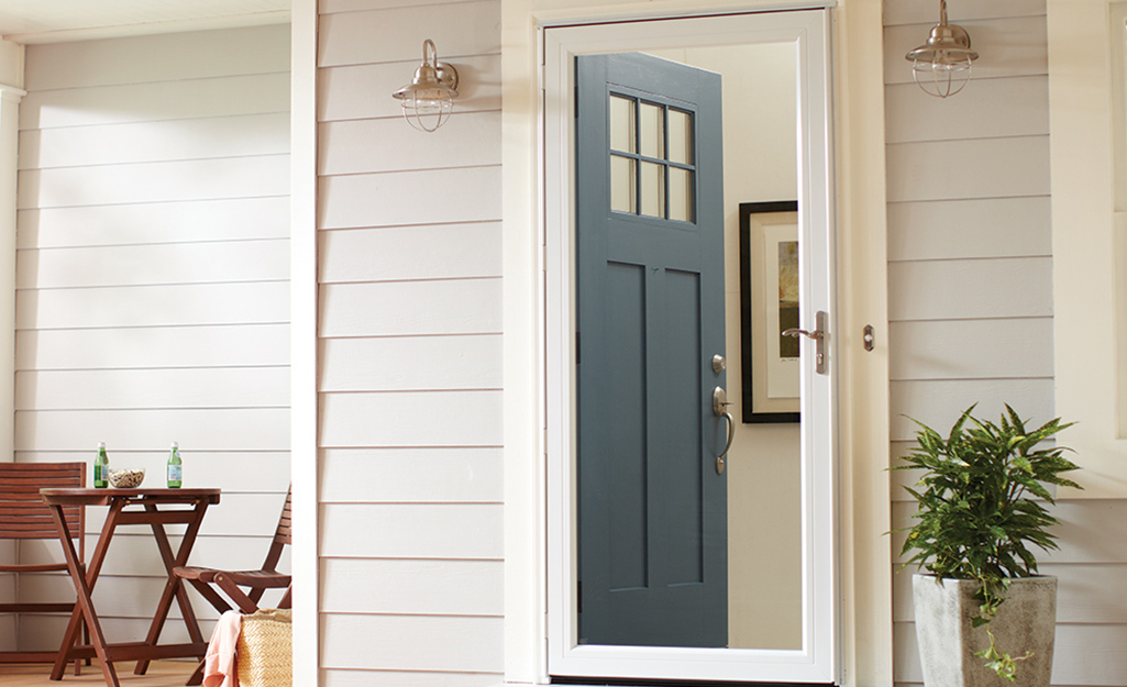 A white storm door installed over a dark teal front door.