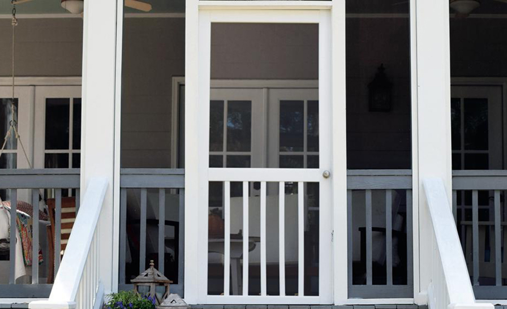 A white screen door as an entrance to a porch.