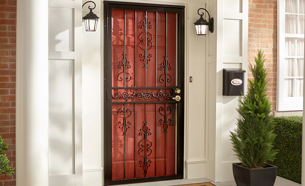 An exterior security door decorated with scrollwork.