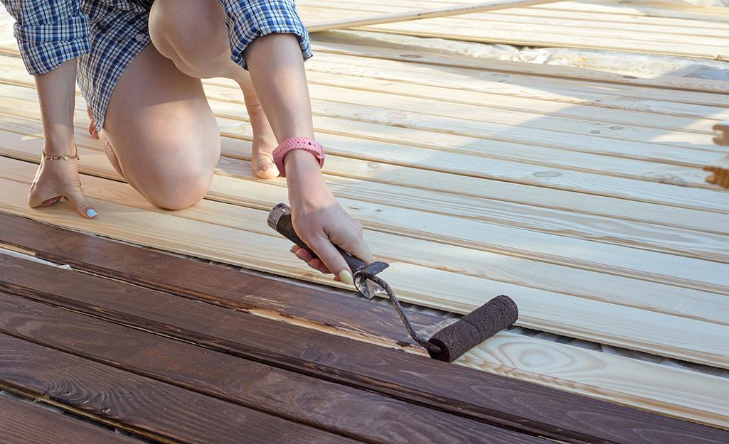 Một người bôi vết gỗ lên sàn tàu.
