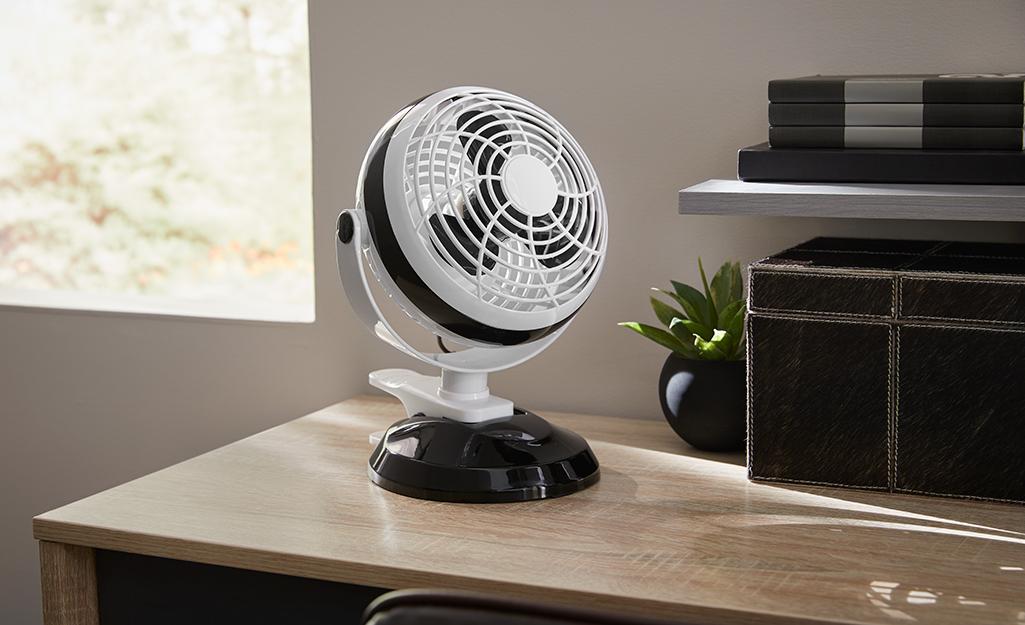 A personal fan positioned on a desk.