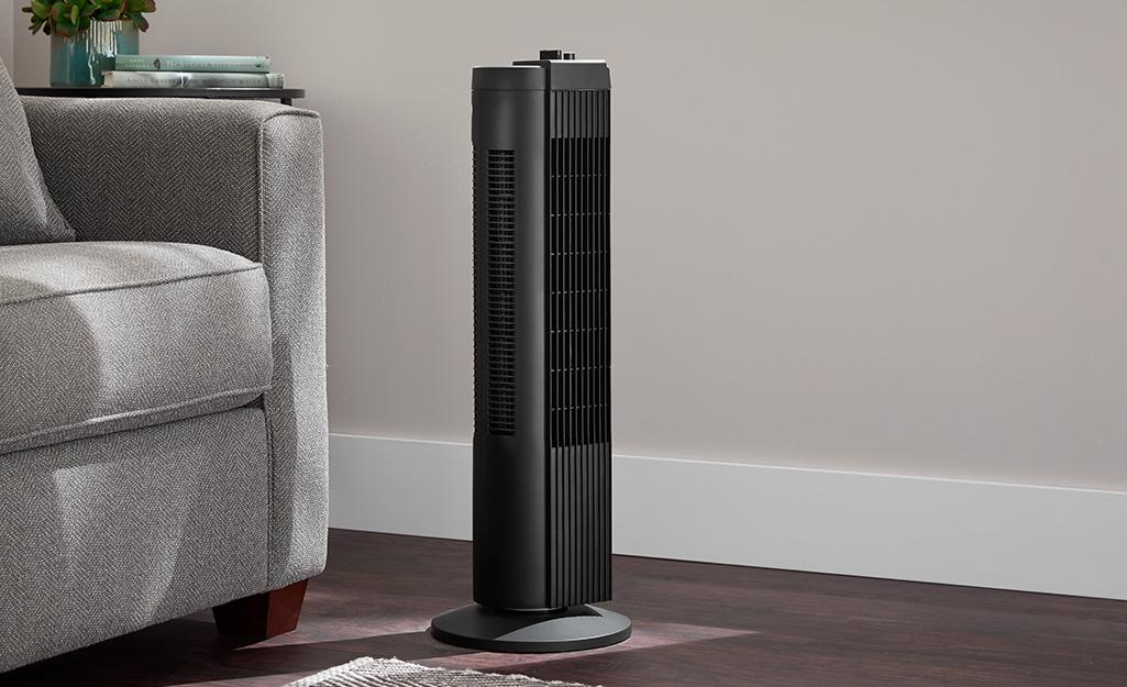 A tower height floor fan in a room.