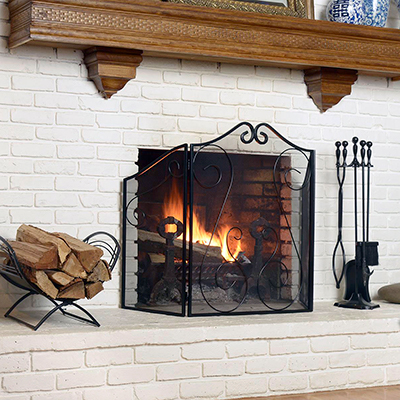 A lit fireplace with accessories around it.