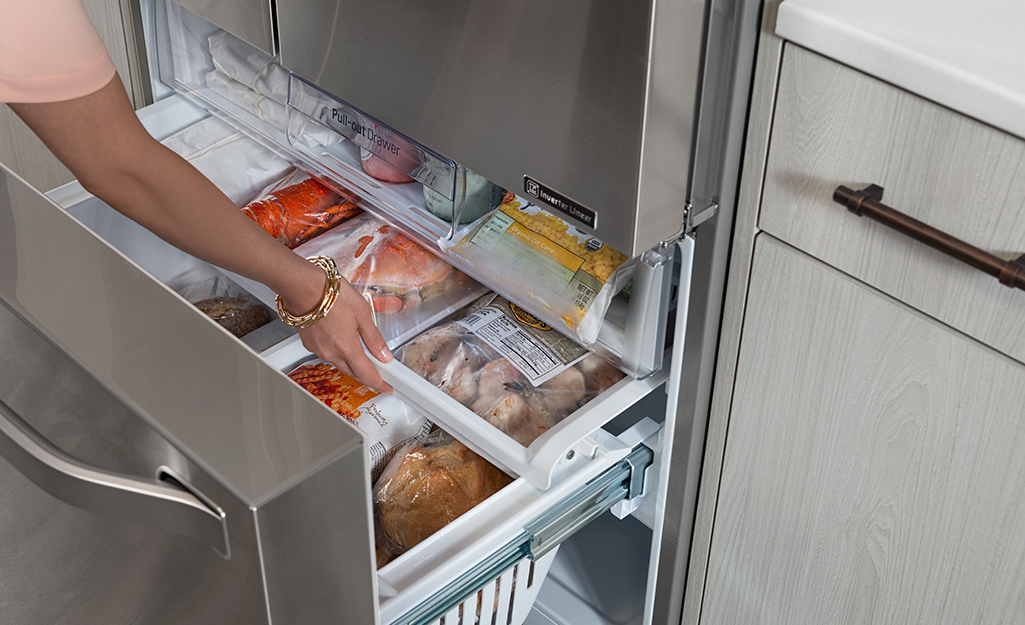 A woman opening a sliding drawer in the bottom half of an upright freezer.