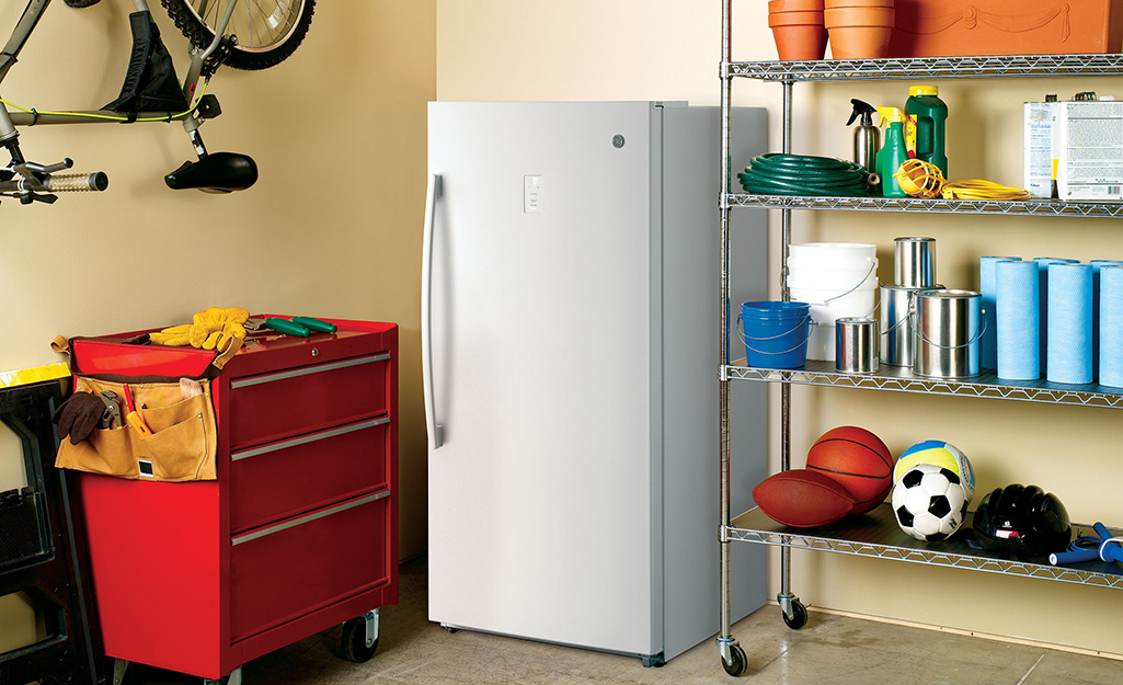 An upright freezer beside a tool chest and a storage rack in a garage.
