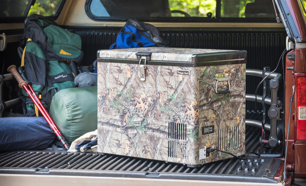A portable freezer with a camouflage design and camping gear in the bed of a pickup truck.