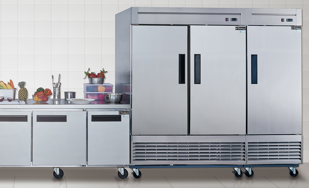A row of single-door and multiple-door commercial freezers on wheels sitting side-by-side.