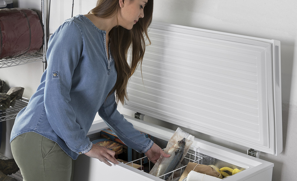 A woman putting frozen food in a wire basket in a chest freezer.
