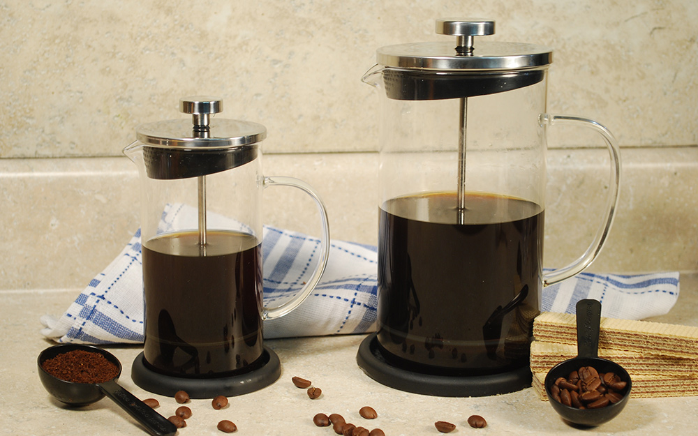 Different sized French presses sitting side by side along with coffee beans and measuring spoons