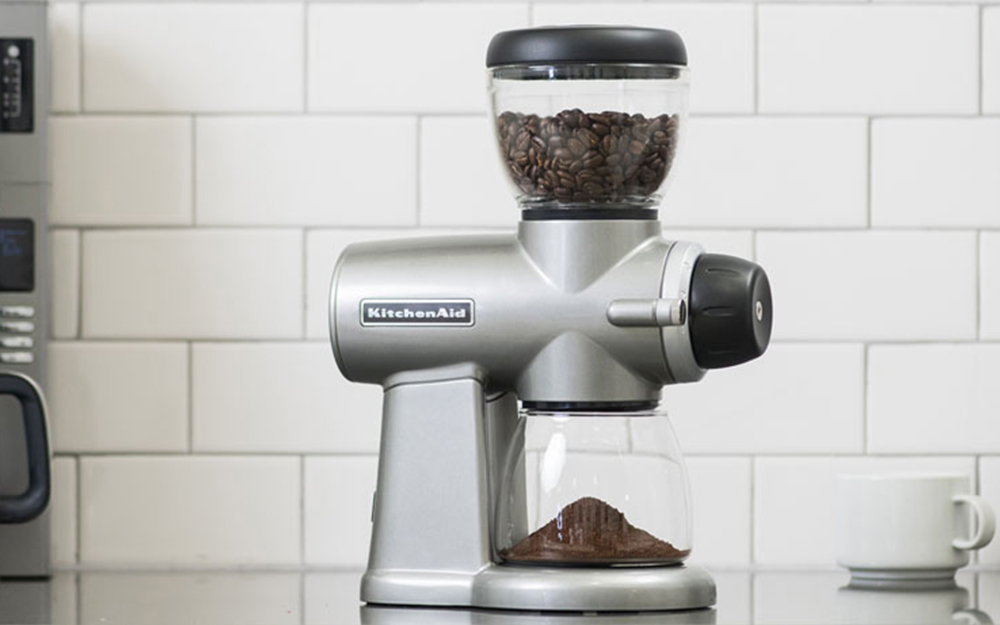 Coffee cup and ground coffee beans next to a coffee cup on a countertop