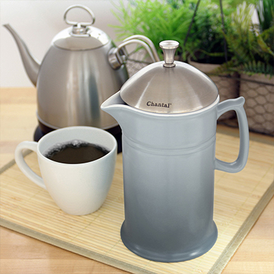 A French press, mug on coffee also coffee pot supported by a countertop