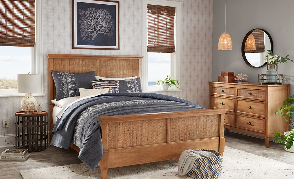 A bedroom styled in earthy tones and medium wood toned furnishings.