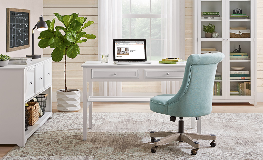 A spacious home office with classic white furniture.