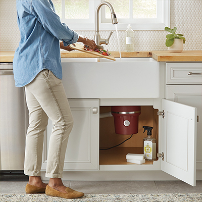 Someone standing in front of a kitchen sink, putting food waste into a garbage disposal that is visible from an open cabinet under the sink.