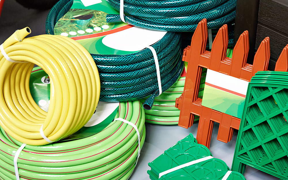 Stacked green and yellow garden hoses.