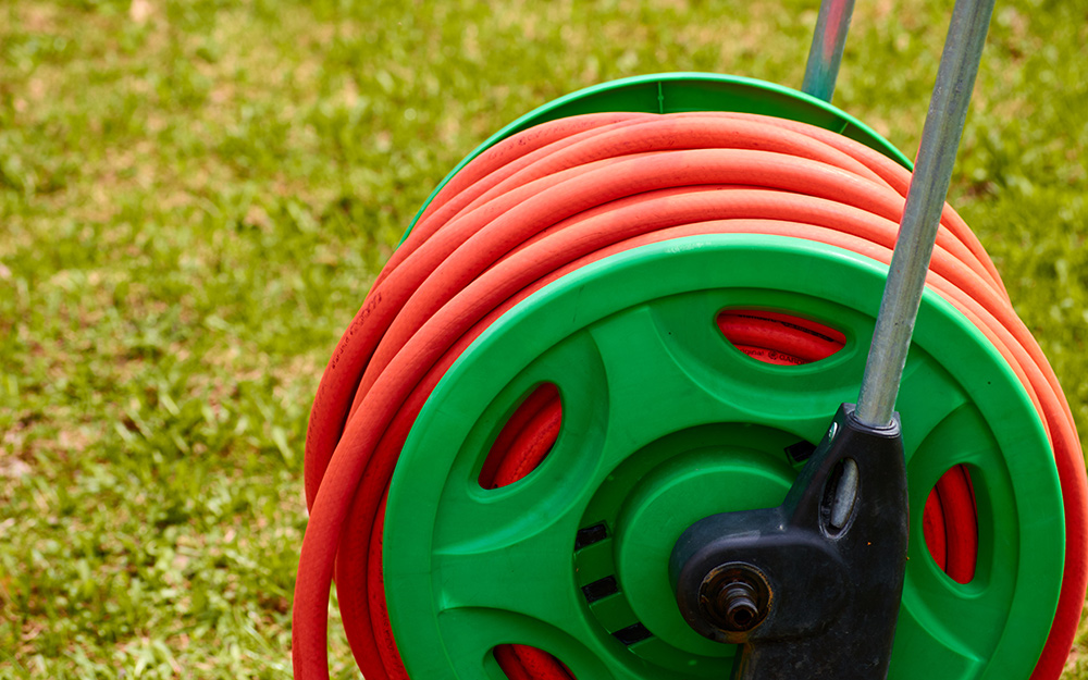 Red garden hose on green hose reel.