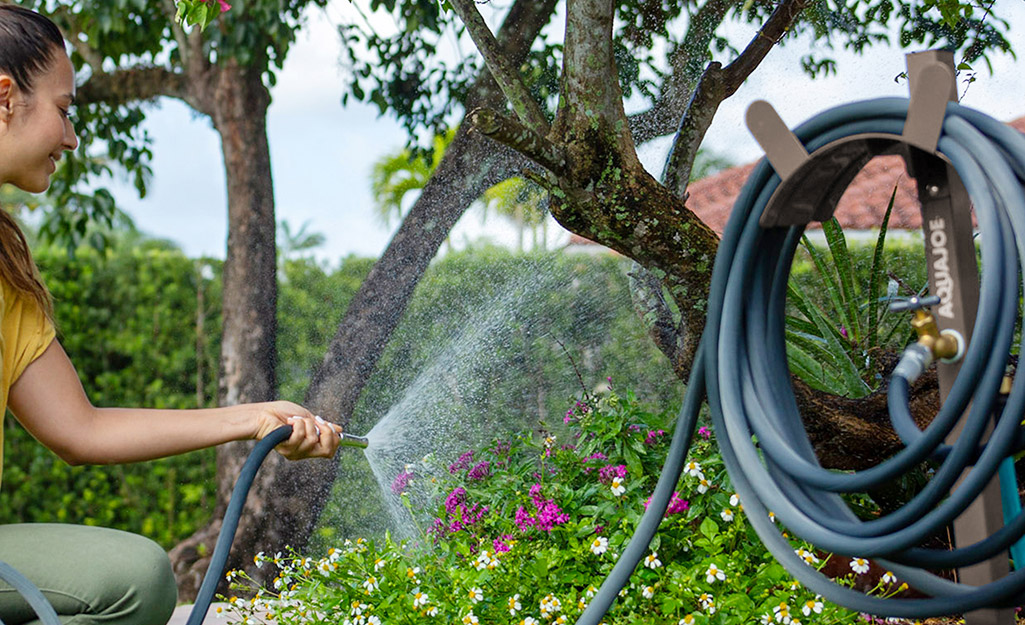 Gardener spraying water with hose and reel