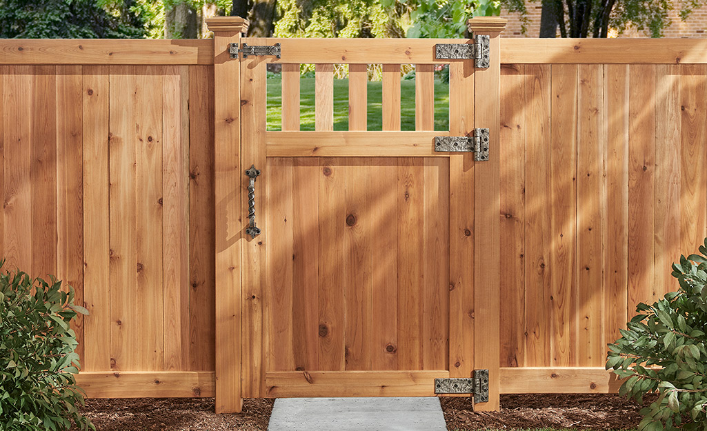 A wood fence gate with textured metal gate hardware.