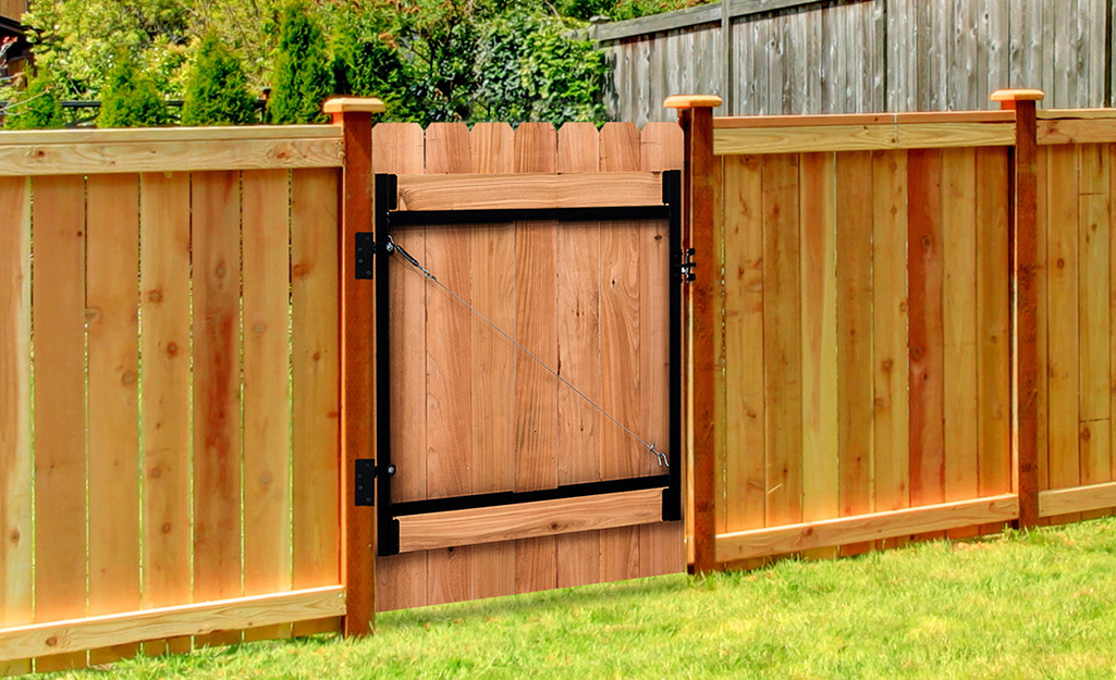 The back of a wood fence gate with anti-sag gate hardware.