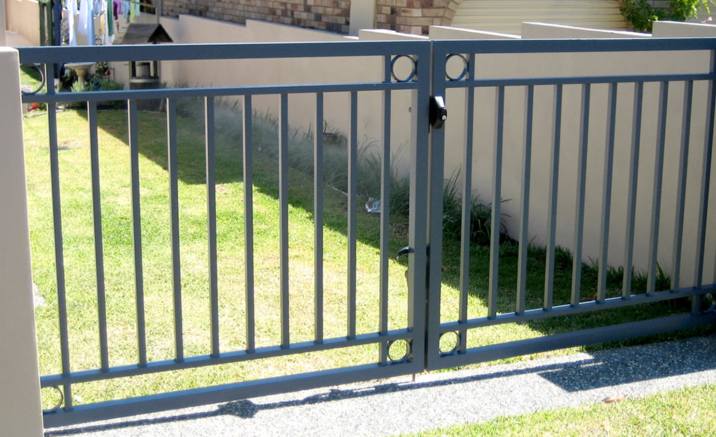 A double swing metal fence gate with a cane bolt and child-resistant latch.