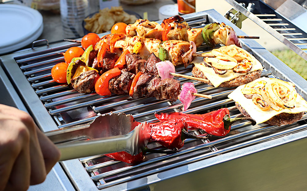 A person uses tongs to flip their grilled vegetables.