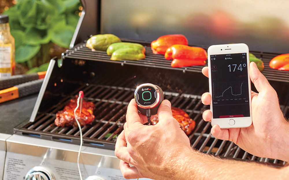 A person uses a wireless meat thermometer.
