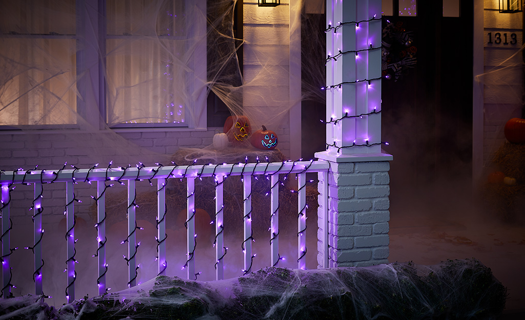 Purple Halloween light strands on a front porch