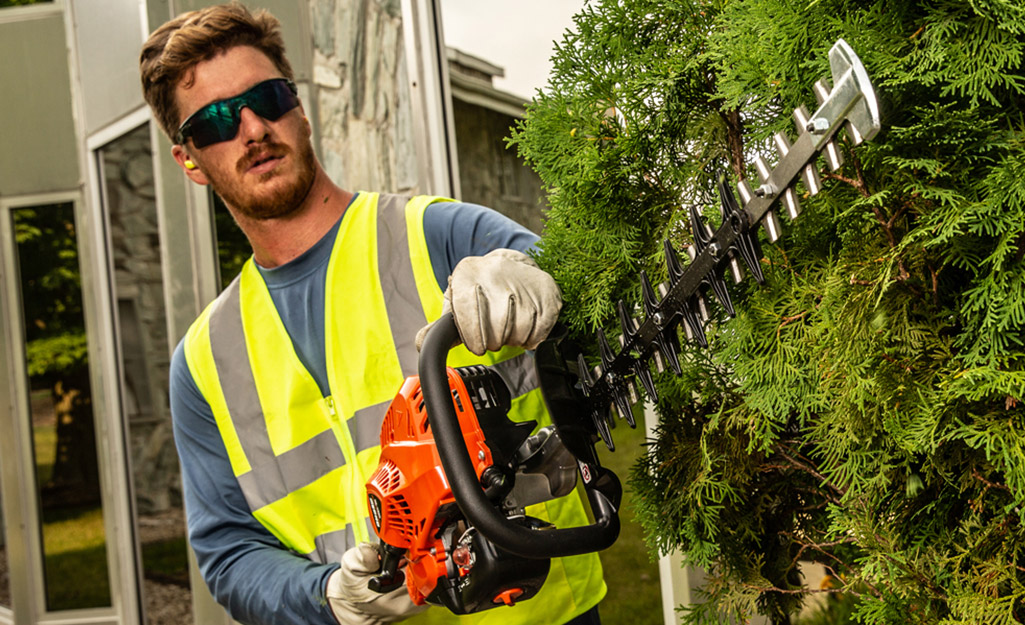 A man wears safety equipment to operate his hedge trimmers.