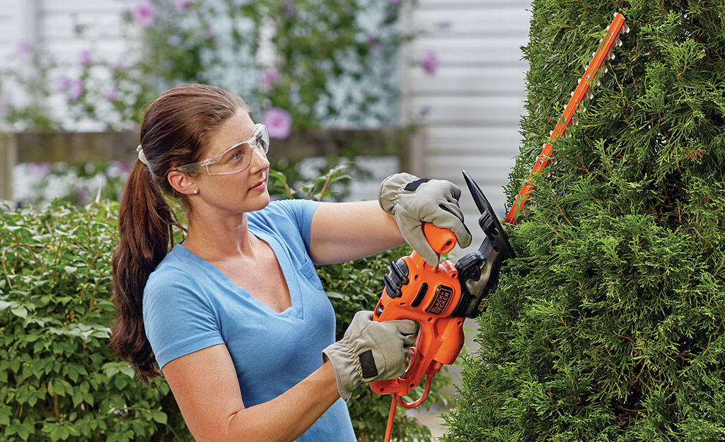 A woman wears safety goggles to trim a shrub in her yard.