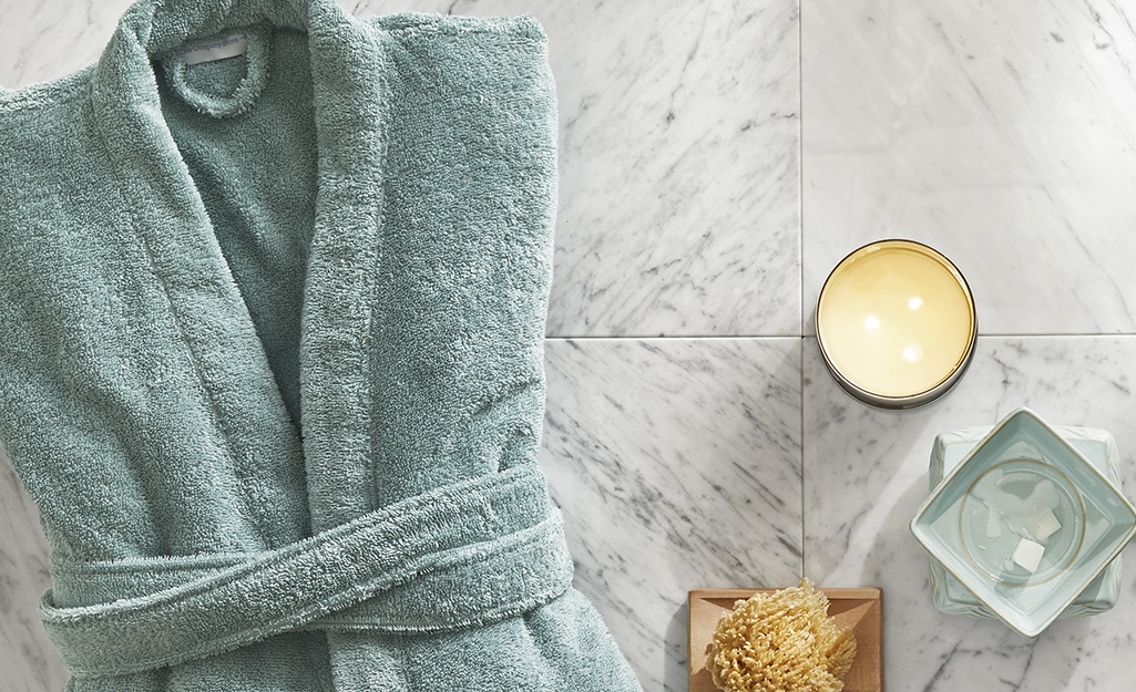 A teal robe sits near a loofah and candle.