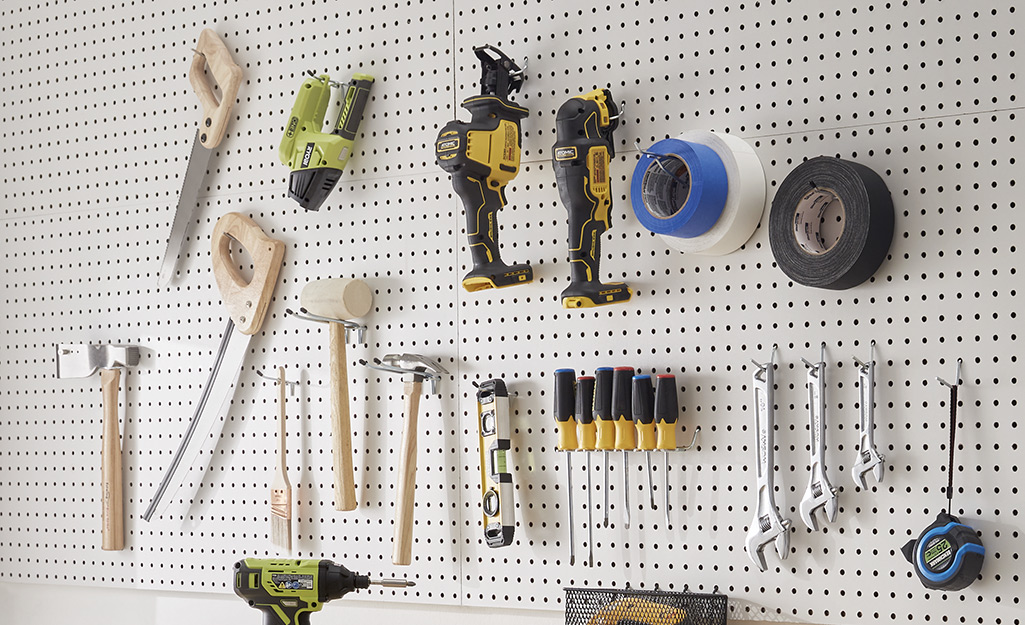 Various tools hang on a pegboard in a garage.