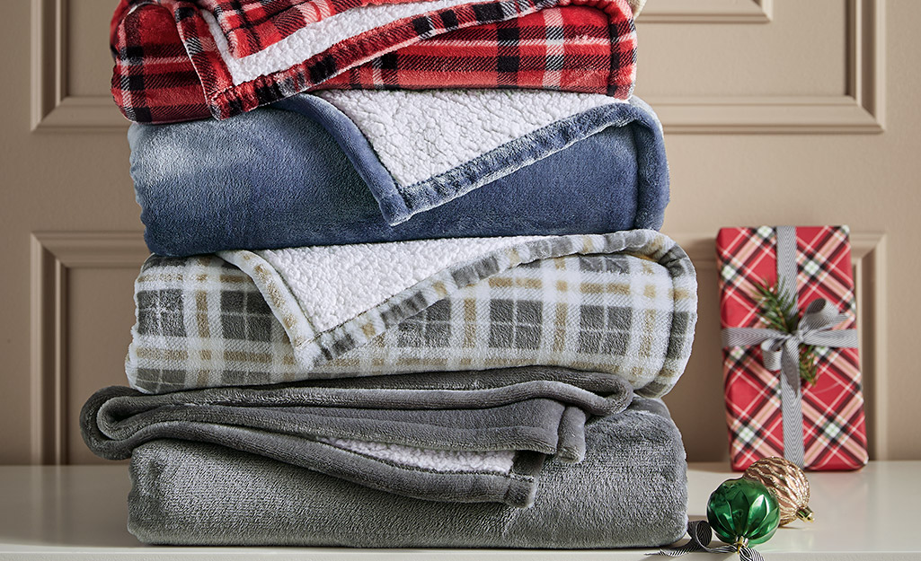 Four stacked blankets in different shades and patterns.