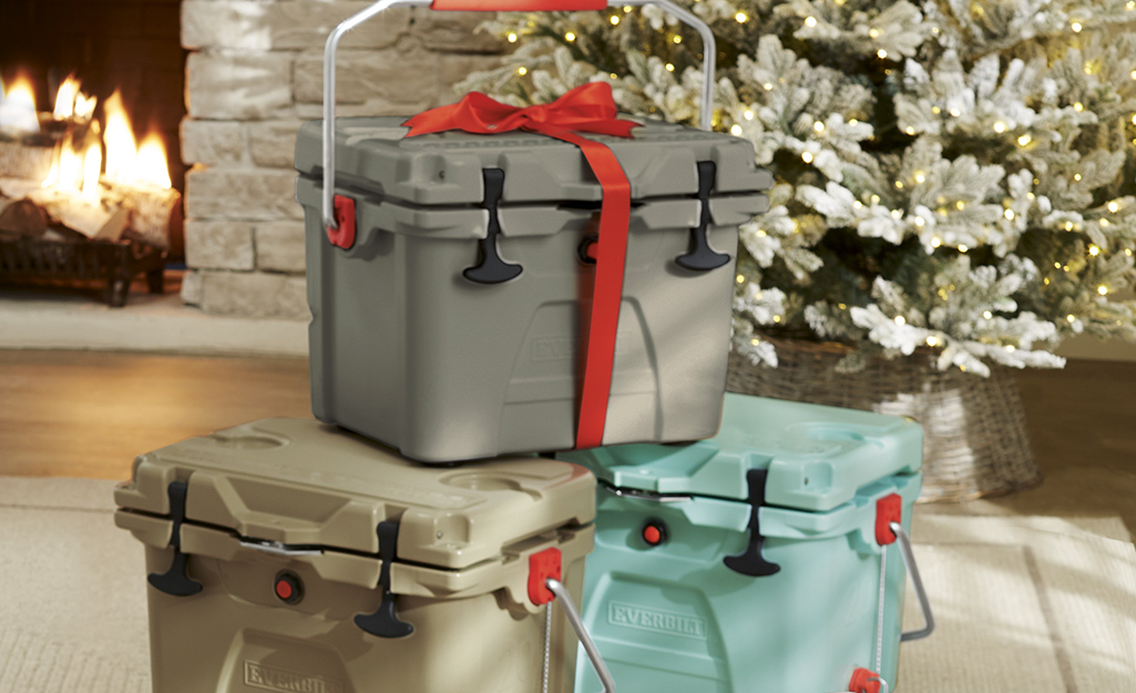 Three coolers sit near a Christmas tree.